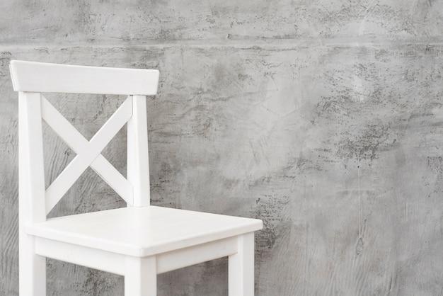 Taburete blanco minimalista de primer plano con paneles de hormigón.