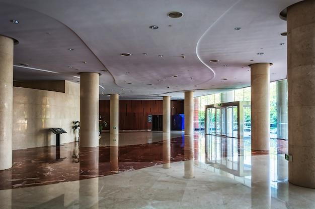 Taburetes elegantes y mesa en salón enorme y luminoso