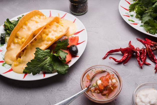 Taco entre verduras en un plato cerca de chili y salsas