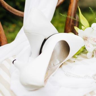 Tacones altos blancos sobre la bufanda en mesa blanca