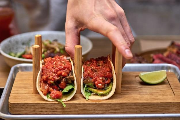 Tacos de cerdo callejeros tradicionales mexicanos con carne de res, aguacate, chile y cebolla en tortilla de maíz amarillo.