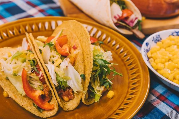 Tacos frescos con carne y verduras en plato marrón.