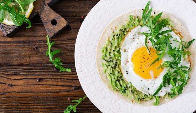 Tacos con guacamole, huevo frito y rúcula. comida sana. desayuno útil endecha plana. vista superior