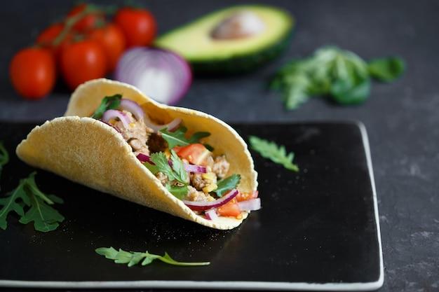 Tacos mexicanos con carne de cerdo, verduras y especias en una placa de piedra negra sobre un fondo oscuro con ingredientes para tacos