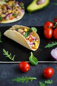 Tacos mexicanos con carne de cerdo, verduras, tomates, aguacate y especias en una placa de piedra negra sobre un fondo oscuro con ingredientes para tacos