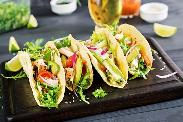Tacos mexicanos con carne de pollo, aguacate, tomate, pepino y cebolla roja.