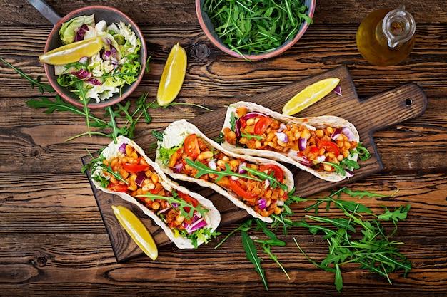 Tacos mexicanos con carne de res, frijoles en salsa de tomate y salsa. endecha plana. vista superior.