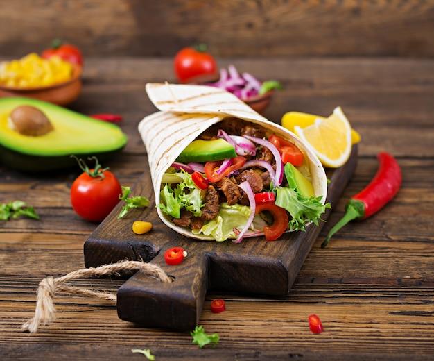 Tacos mexicanos con carne de res en salsa de tomate y salsa de aguacate