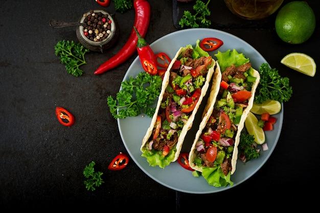 Tacos mexicanos con carne de res en salsa de tomate y salsa