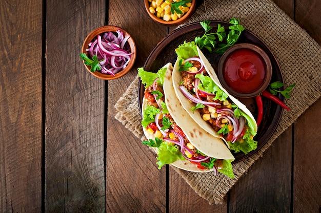 Tacos mexicanos con carne, verduras y cebolla roja.
