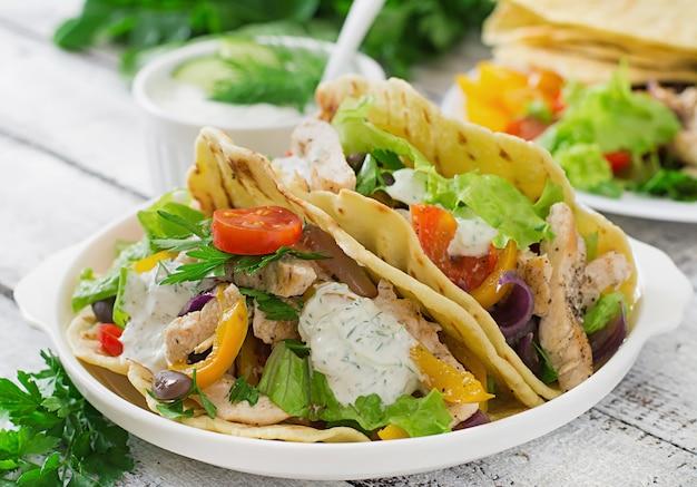 Tacos mexicanos con pollo, pimientos, frijoles negros y vegetales frescos.