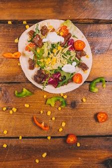 Tacos mexicanos con ternera y verduras en escritorio marrón.