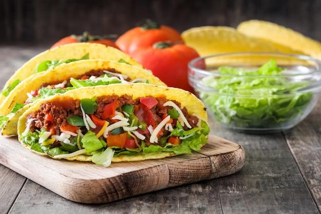 Tacos mexicanos tradicionales con carne y verduras en madera