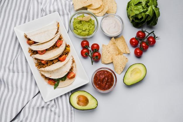 Tacos en el plato entre la servilleta junto a las salsas y verduras