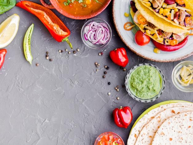 Tacos y quesadilla junto a tazas con verduras.