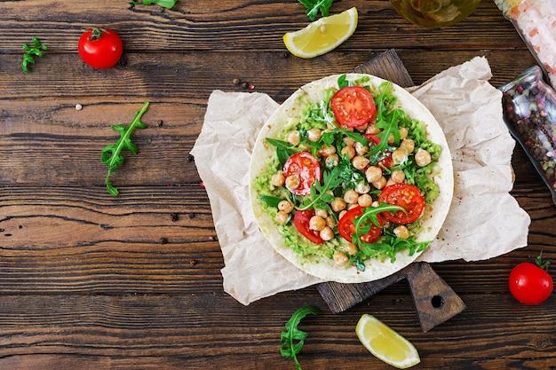 Tacos veganos con guacamole, garbanzos, tomates y rúcula. comida sana. desayuno útil endecha plana. vista superior