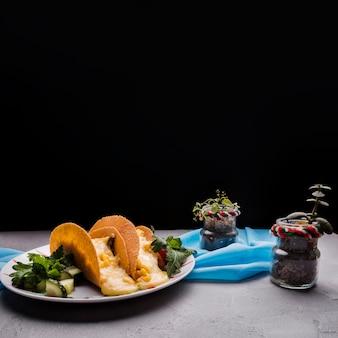 Tacos entre las verduras en el plato cerca de las plantas de interior y la servilleta en la mesa