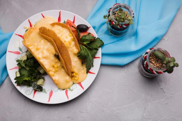 Tacos entre las verduras en el plato cerca de las plantas de interior y la servilleta