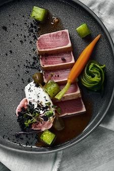 Tagliata de atún en vegetales zanahorias y pimientos guisados, hermosa porción, cocina tradicional italiana