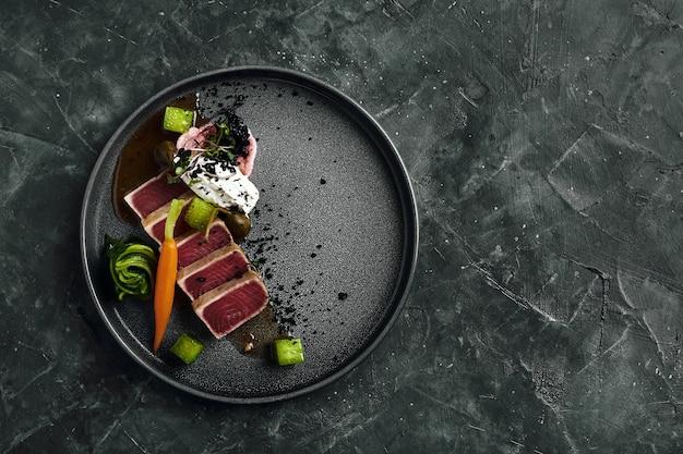Tagliata de atún en verduras zanahorias y pimientos guisados