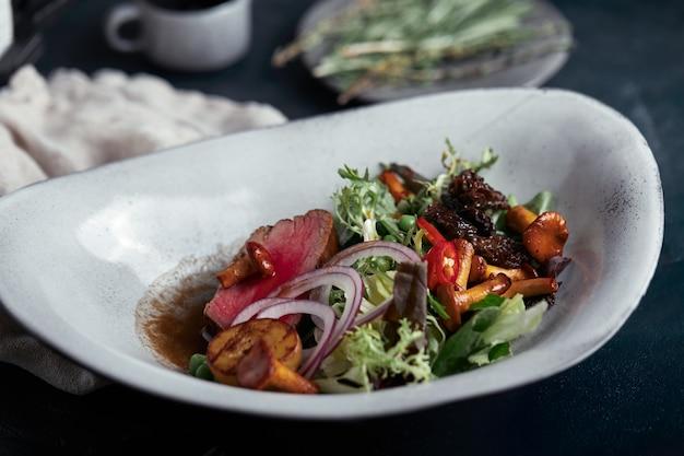 Tagliata de ternera con verduras. primer plano, bajo perfil, gris.