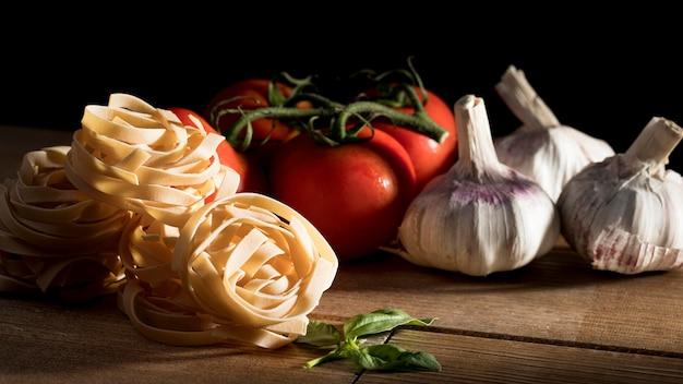 Tagliatelle con albahaca y verduras en el escritorio