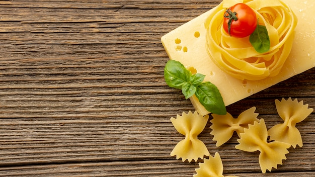 Tagliatelle farfalle crudo con albahaca, hojas de queso duro, tomates y espacio de copia