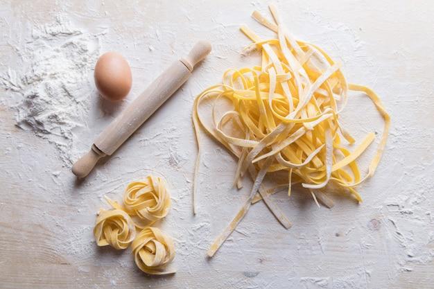 Tagliatelle hecho en casa crudo italiano fresco de las pastas en la tabla de madera. pasta italiana hecha de harina, agua y huevos.