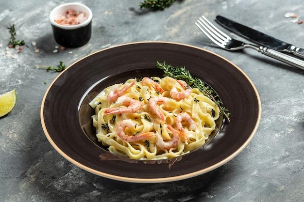 Tagliatelle de pasta con camarones a la plancha, salsa bechamel y tomillo, pasta fettuccine. comida italiana. fondo de receta de comida. de cerca.