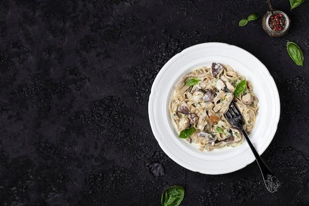 Tagliatelle de pasta casera con champiñones, salsa pesto y nata