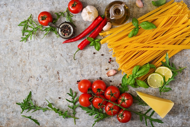 Tagliatelle de pasta e ingredientes para cocinar (tomate, ajo, albahaca, chile). vista superior