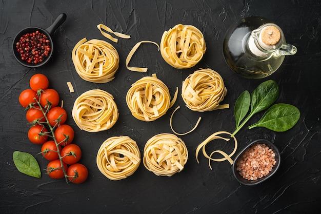 Tagliatelle de pasta con ingredientes, en mesa de piedra negra, vista superior plana
