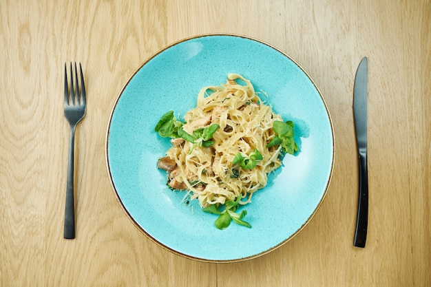 Tagliatelle con pollo, salsa blanca y parmesano en un tazón azul sobre la mesa de madera. pasta italiana casera tradicional. de cerca