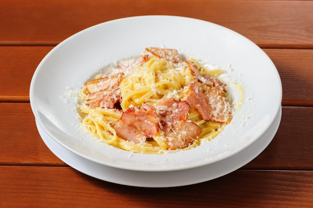 Tagliatelli carbanara cocina italiana en placa rústica mesa de cocina de fondo