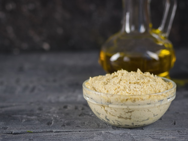 Tahini de pasta fresca de semillas de sésamo con aceite de oliva y ajo en una mesa de madera negra.