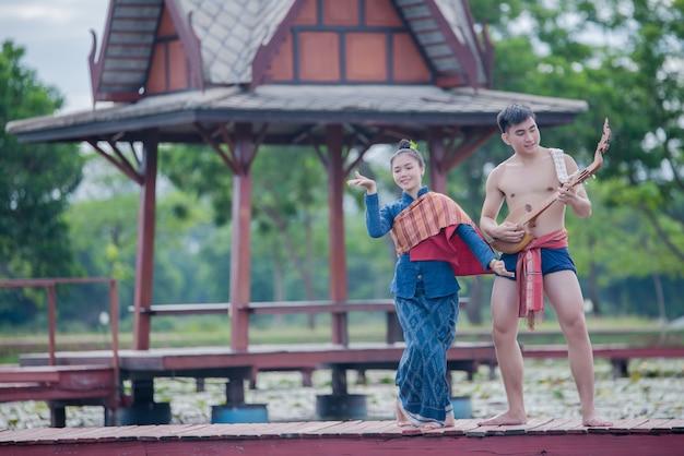 Tailandia mujeres y hombres en traje nacional con pin de guitarra (instrumento de cuerda pinchada)
