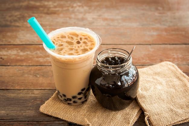 Taiwán té con leche helada y burbuja boba en el vaso de plástico y boba en el frasco de vidrio