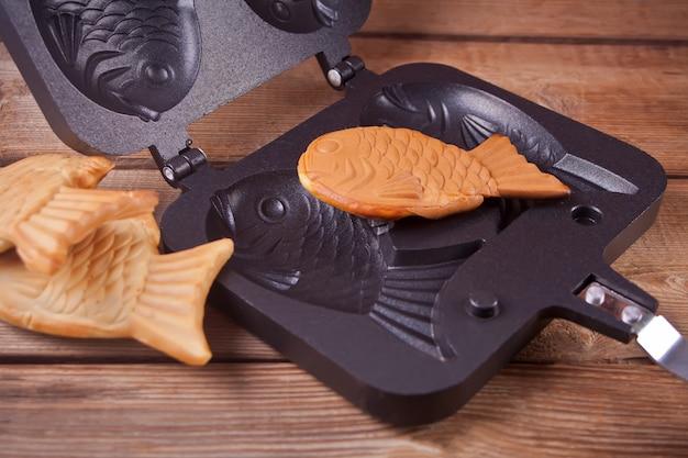 Taiyaki comida de la calle japonesa en forma de pescado relleno dulce waffle sobre madera