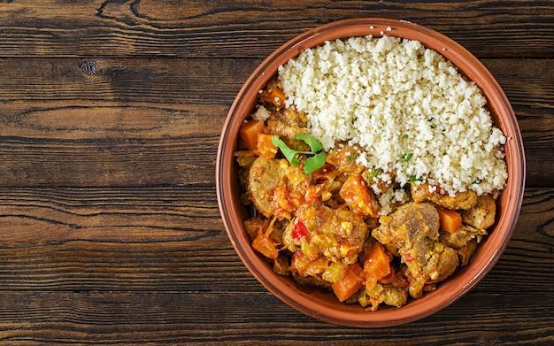 Tajine platos tradicionales, cuscús y ensalada fresca en la mesa de madera rústica. tagine de carne de cordero y calabaza. vista superior. lay flat