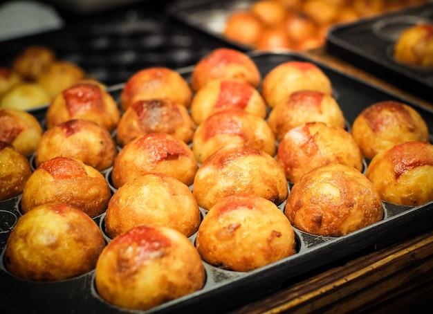 Takoyaki está cocinando en una sartén caliente. comida callejera japonesa famosa.