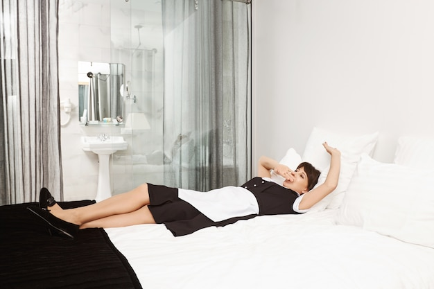 Tal vez debería tomar una siesta antes de que vengan los clientes. foto de mujer cansada en uniforme de mucama acostada en la cama y bostezando, cubriéndose la boca, agotada después de limpiar todo desorden que los clientes dejaron en su habitación de hotel