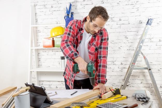 Taladro de carpintero en tablón, en su taller