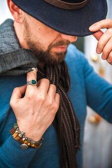 Talismanes, amuletos en la mano de un hombre. un hombre con un suéter azul y una bufanda.