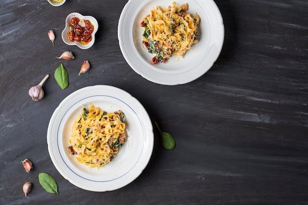 Tallarines de boniato de pasta italiana con tocino, tomates secos y espinacas