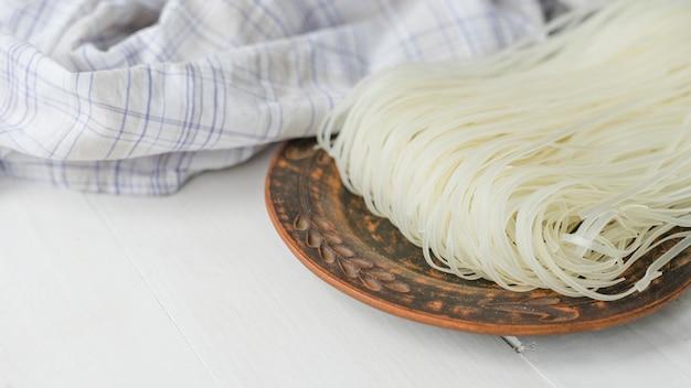 Tallarines de fideos de arroz secos en un plato circular cerca de un paño a cuadros sobre una superficie blanca