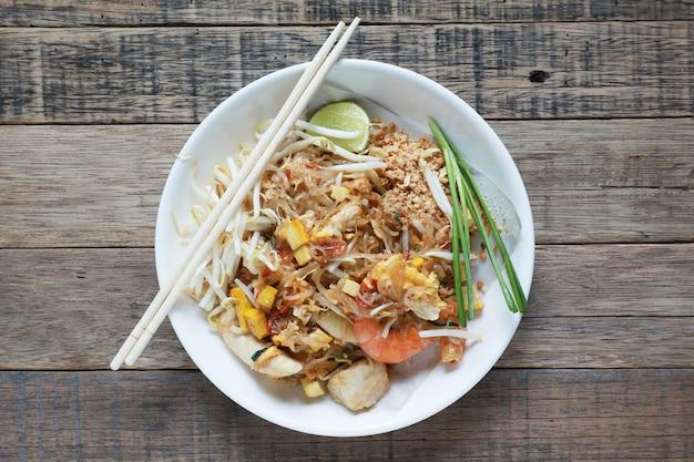 Tallarines fritos al estilo tailandés con langostinos tailandia llamada pad thai, tallarines salteados al estilo tailandés en la mesa de madera.