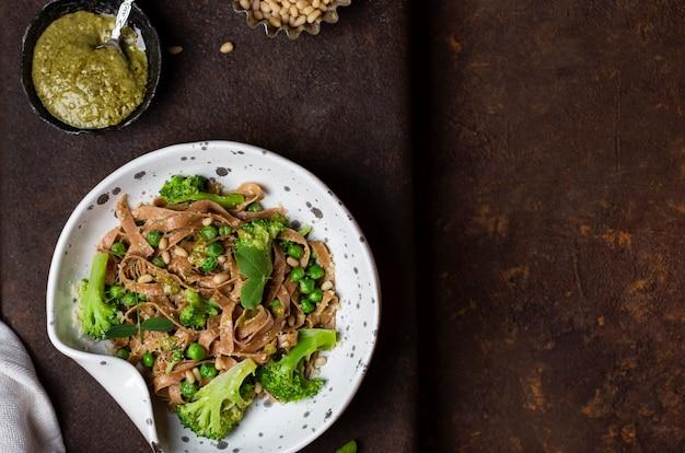 Tallarines integrales con pesto, guisantes y brócoli