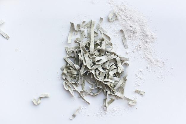 Tallarines de pasta cubiertos por harina con un rodillo de madera sobre un fondo blanco