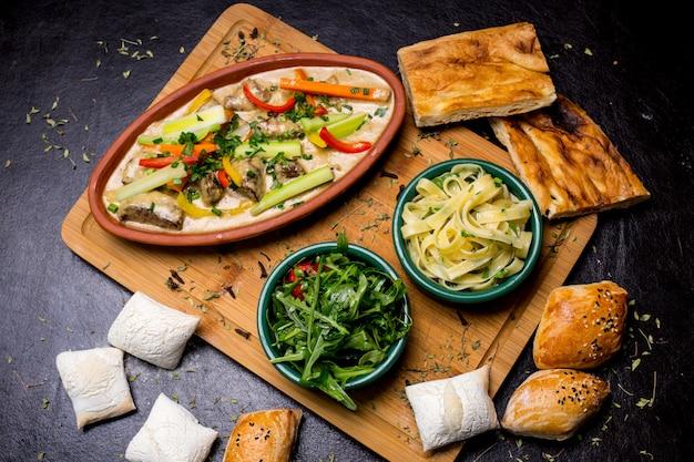 Tallarines con pescado sobre tabla de madera crema verduras rúcula bollos tomate vista superior