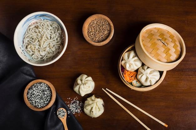 Tallarines de udon con semillas de sésamo; semillas de cilantro con albóndigas y palillos en mesa de madera